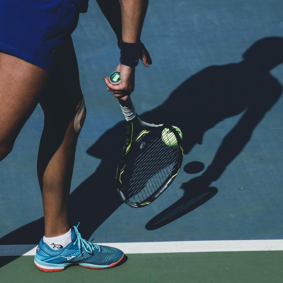 Tennis Player Bouncing Ball
